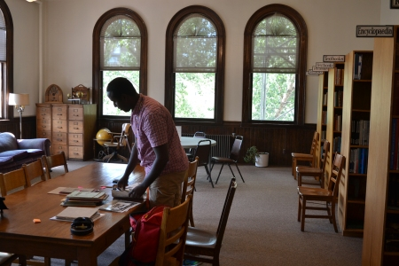 Bashir looks through a stack of papers on a table in a reading room.
