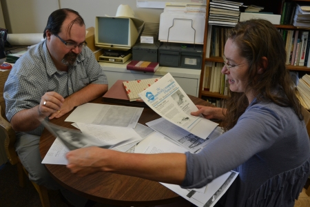 Ron Kelland digs through a stack of papers with Christy in his office