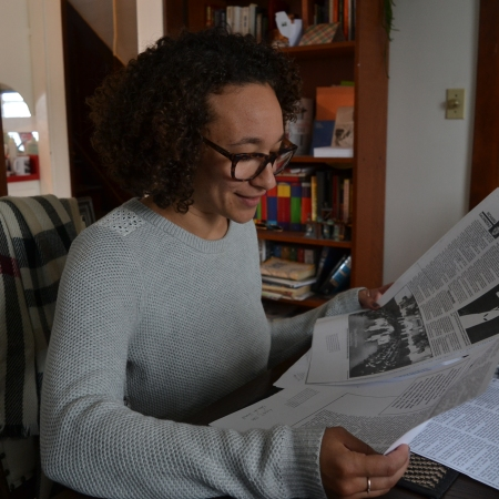 "Rebecca holds up a photocopy of an old newspaper article: ""Alberta's Ku Klux Klansmen"" by Richard DeCandole"