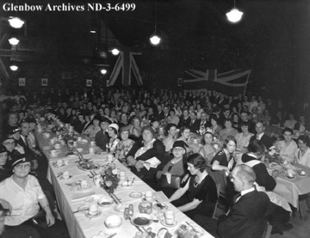 A crowd sits at packed dining tables, with British flags hung behind them.