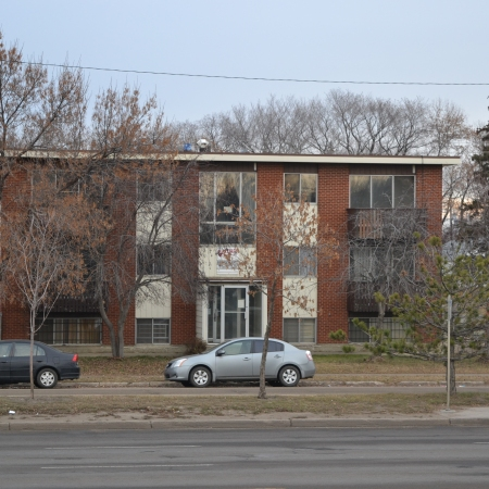 A two and a half story apartment building viewed from across the street, with bare trees all around and a clear blue sky.