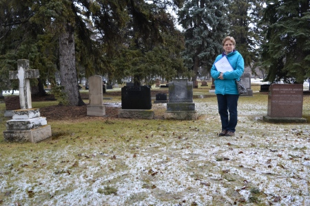 A wide angle of the slush and grass at Frank Beevers' gravesite - Sheila Thomas stands to one side, holding a file of information about him.
