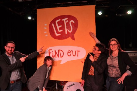 Dave Cournoyer, Sarah Hoyles, Chris, and Kisha Supernant in front of the Let's Find Out sign.