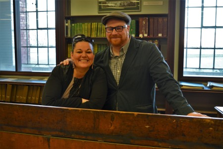 Jodi Stonehouse and Nathan Smith smile at the camera behind a desk at the City of Edmonton Archives