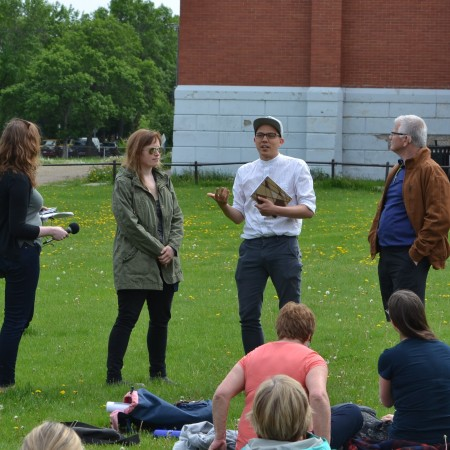 Sam records while Morgana, Chris, and Robert Geldart talk in the field outside Ritchie School.