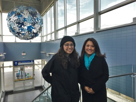 Lauren Crazybull and Sandy Pon stand inside the LRT station at Century Park, with a globe of blue leaves behind them.