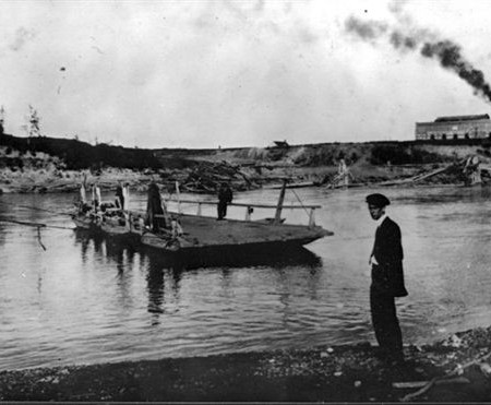 A flat wooden ferry moves towards the shore, and a figure stands on the bank.