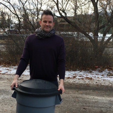 Jason Harcus, holding a rubber garbage bin in his back alley.