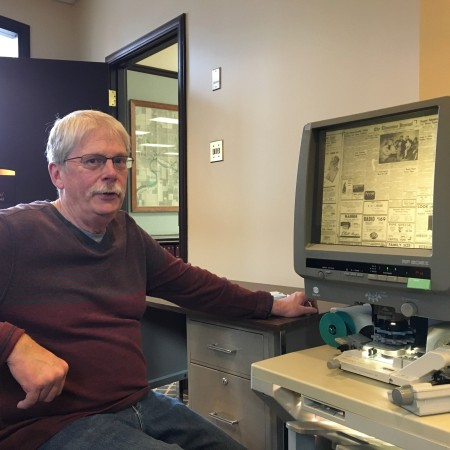 Glen Carlson is seated, looking at the camera, sitting in front of a microfilm reader