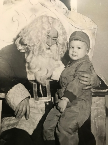 Black and white photo. Glen as a small child looks at the camera while he sits on the lap of Santa, who has a HUGE beard and belt buckle.