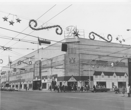 A glitzy-looking shot of the Bay at Christmas in the 1960s, with a village facade wrapped around the building. The Bay logo has a Jetsons' feel, and there are stars and pine swirls hanging from the power lines above the street.