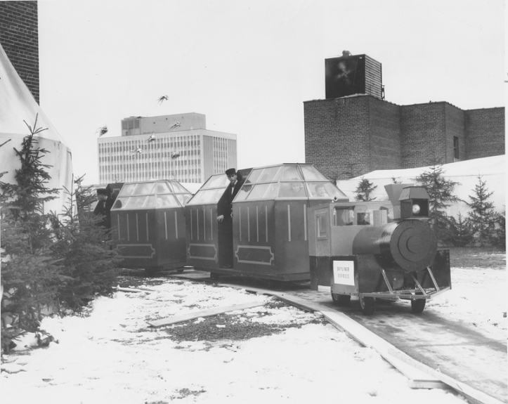 The train running around the snowy roof, with figures inside behind the windows. [Hudson's Bay Company Archives, HBCA 1987-363-E-610 - 51]