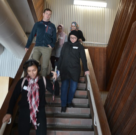 Rasha holds a microphone and wears headphones as she leads the way to Mike's building, with teacher Ian Potts behind her, as well as Laila, Mariam, and Nuha.