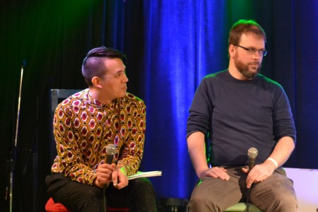 Chris and Dan sit with microphones on stage