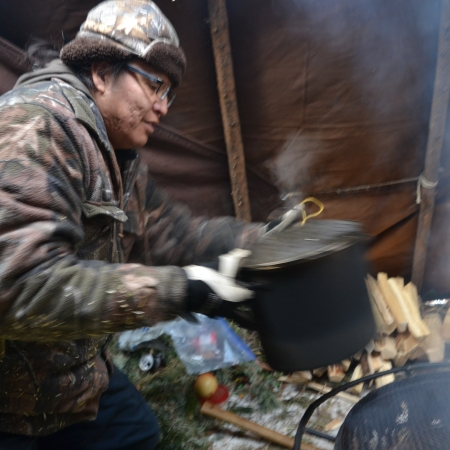 Dwight Paul setting a pot of deer ribs on the fire inside a hunting camp tent at Silverskate.