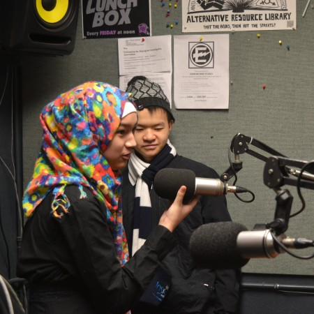 Mariam trying out the mics in the on-air booth at CJSR, with Andrew Hui in the background.