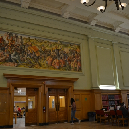 A wide angle shot of the reading room in the Rutherford Library that contains Glyde's mural. A student is walking through the doors underneath it, and other students are sitting at tables studying nearby.