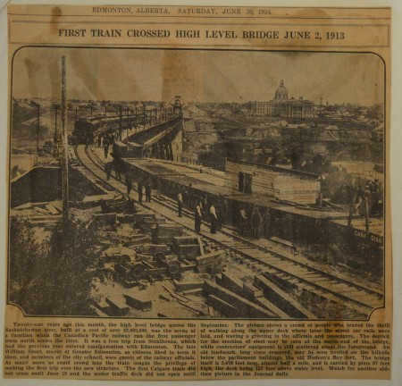 A yellowed newspaper page from 1934, featuring an image of a train crossing the High Level Bridge from the south side.