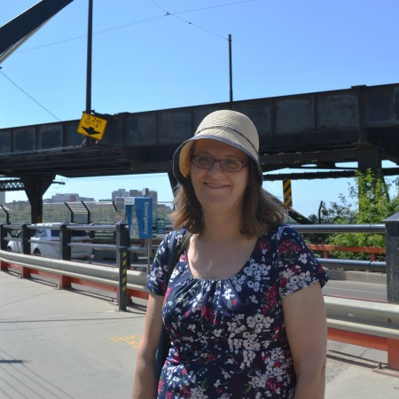 Karen Simonson stands in front of the north side of the High Level Bridge.