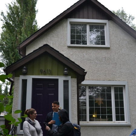 Nicole Anderson speaks to Chris and Oumar outside of her house as the tour group waits to enter
