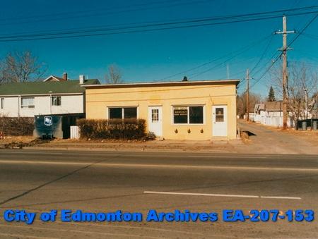 A flat rectangular building overlooks an empty residential street