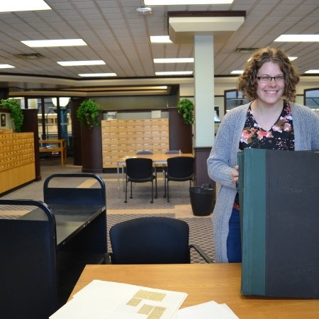 Meribeth Plenert poses with the Edmonton Journal book from March 1953. It's sitting on a table propped up, and it's almost chest-high on Meribeth.
