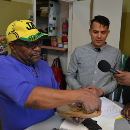 Mike Wallace wears a bright yellow and green Jamaica hat and shows off a last inside his shop