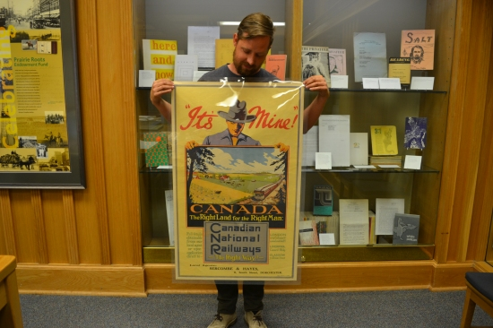 The poster reads: It's Mine! And a man holds a picture of a prairie farmstead.