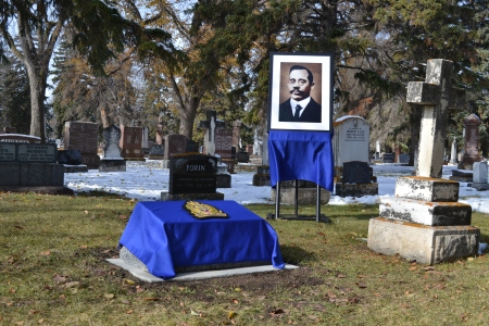 Frank Beevers' touched-up portrait stands in a glass frame on an easel beside his new gravestone, covered by a blue cloth and the Edmonton Police Service logo.