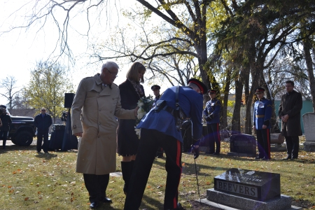 Graham and Candy stand behind a police officer laying a wreath by the new gravestone.