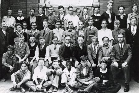 A black and white photo of four rows of male students. All of the students are white except for one sitting at in the centre of the front now.