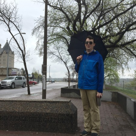 Allan stands holding an umbrella along a walkway, with the Hotel Macdonald in the background. To Allan's left, you can see the conrete plinth where the plaque/panel used to be.