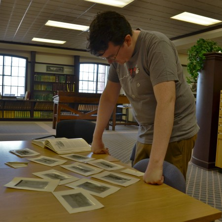Allen looks at a pile of about ten photos at the City of Edmonton Archives