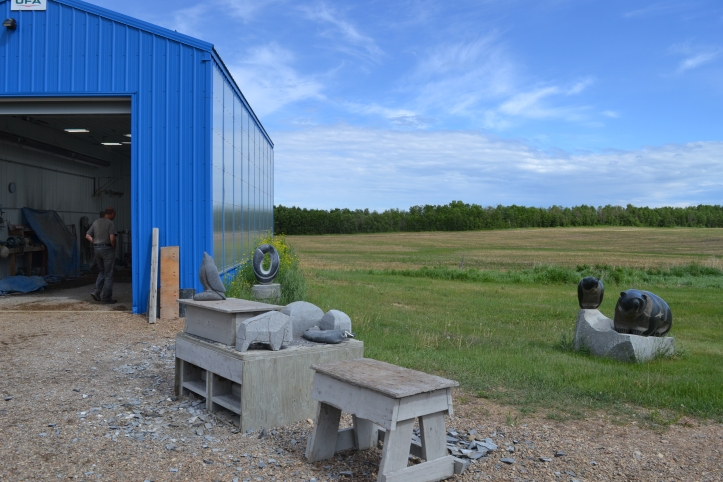 Carvings in progress of various sizes in front of a blue shed