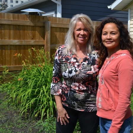 Karen Haugen-Kozyra, President of Viresco Solutions, stands in the garden in front of lilies together with Denise.