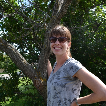 Brooklin smiles with sunglasses in front of Capilano apricot tree #1