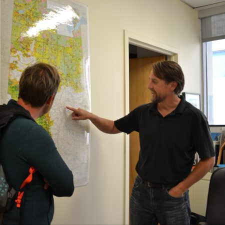 Dustin Bajer and Scott Nielsen look at a map of Alberta in Scotts office