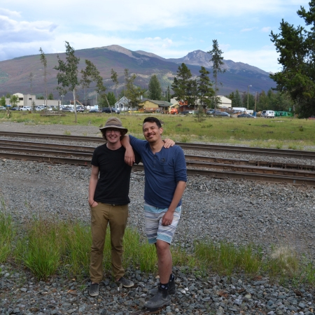 Dylan and Chris smile in front of train tracks in Jasper