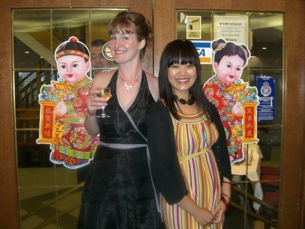 Two women stand back to back in front of glass doors inside a restaurant, smiling