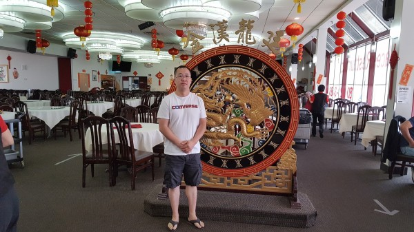 Thomas Ly stands in casual clothing in front of a circular ornament, inside Dynasty Restaurant, with social distancing arrows on the floor.