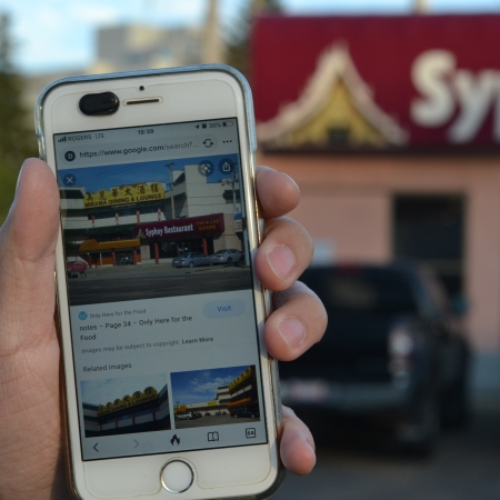 A photo of Nathan holding a phone with an image of the Mirama restaurant behind Syphay Restaurant. Behind Nathan's hand is the present-day Syphay Restaurant, with no Mirama building.