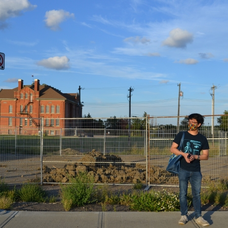 A photo of Reporter Nathan Fung in front of the site where the Mirama restaurant once stood, with Alex Taylor School in the background.