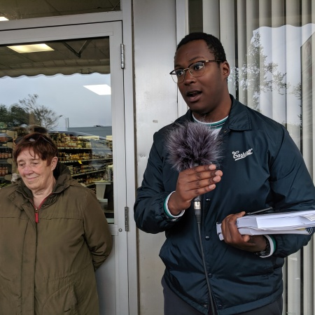 oumar salifou speaks into a microphone in front of a store, with a tour participant beside him